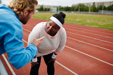 Oversized woman listening to her trainer consultation during workout at stadium