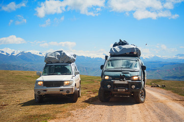 Two cars of travelers on mountain snow road landscape. 4x4 jeep car  on a mountain pass, mount peak. Extreme dangerous adventure