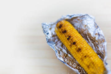 Baked yellow corn in foil on white background