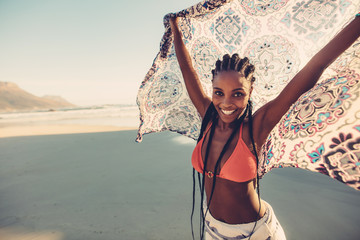 African female standing on the seaside with scarf