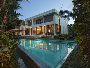 Exterior of home at dusk with pool in foreground