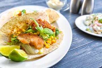 Delicious fish taco on white plate on blue dark table