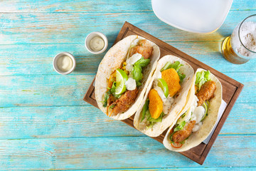 Delicious fish tacos on wooden board on blue background