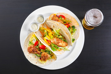 Delicious fish tacos on white plate  with beer on black background