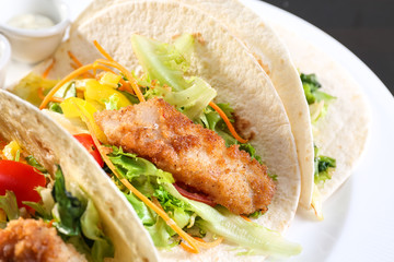 Delicious fish tacos on white plate, close up