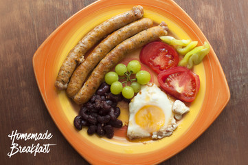 English breakfast in plate with fried egg and meat sausages, beans, grapes, sliced tomatoes and pepper