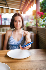 The girl in the restaurant holds out the phone.