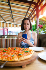 The girl is making pizza photos on the phone.