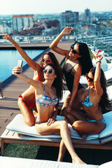 Four young women in a penthouse near the pool doing selfi in a bikini