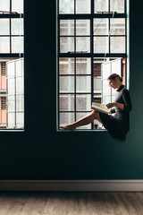 Woman sitting on window sill and reading book