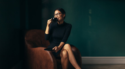 Happy businesswoman drinking coffee and looking away