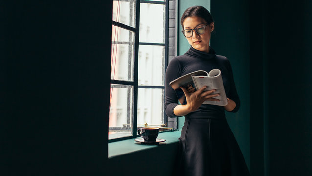 Woman standing by window, reading magazine