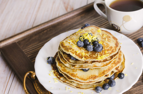 Pancakes with blueberry on white plate.