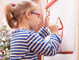 girl with glasses and a striped t-shirt paints