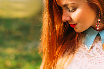 Beautiful woman with long hair and freckles lit by warm sun in t