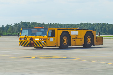 The aerodrome tractor is driving along the steering paths at the airport