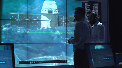People in space mission control center managing spaceship undocking. Elements of this image furnished by NASA.