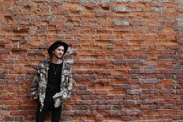 Horizontal lifestyle portrait of happy trendy looking young male hipster posing outdoors against red brick wall background with copy space for your content, wearing hat, jeans and camouflage bomber