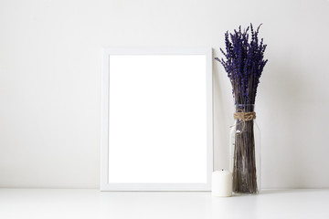 Beautiful cozy shot of white table in living room or home office desk with glass vase or bottle with dried lavender flowers, candle and empty picture frame with copy space for your photograph