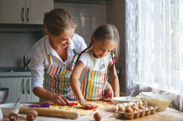 Happy family mother and daughter bake kneading dough in kitchen