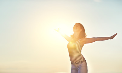 Happy woman opened her hands against sky in summer in nature
