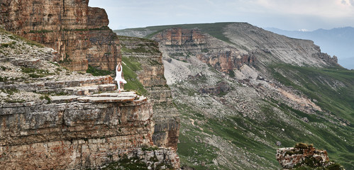 Wall Mural - woman practices yoga and meditates   on mountains