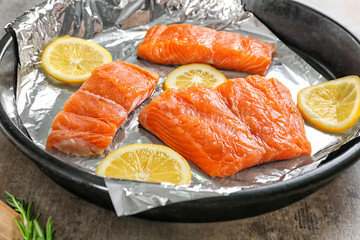 Frying pan with foil, slices of lemon and salmon, closeup