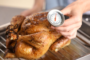 Photo sur Aluminium Viande Young woman measuring temperature of whole roasted turkey with meat thermometer