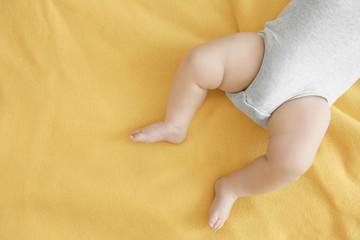Little legs of cute baby sleeping on bed