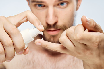 Man with a beard on a light background applies cosmetic cream on the little finger hands, portrait