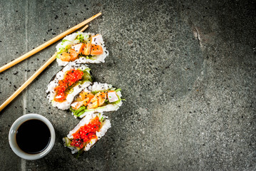Trend hybrid food. Japanese Asian cuisine. Mini sushi-tacos, sandwiches with salmon, hayashi wakame, daikon, ginger, red caviar. Black stone table, with chopsticks, soy sauce. Copy space top view