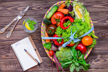 Top view Big Basket with different Fresh Vegetables tied with measuring tape, glass of water and notebook on the wooden table. Healthy lifestyle concept. Detox, diet. Selective focus. Space for text