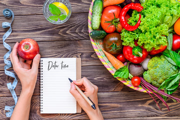 Female hands make notes in diet book on the wood table with Basket of different Fresh Vegetables, measuring tape, glass of water. Healthy lifestyle concept. Detox, diet. Selective focus. Copy space