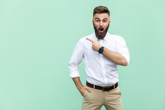 Wow! Handsome young adult man with beard in shoked. Pointing away while standing isolated on light green background
