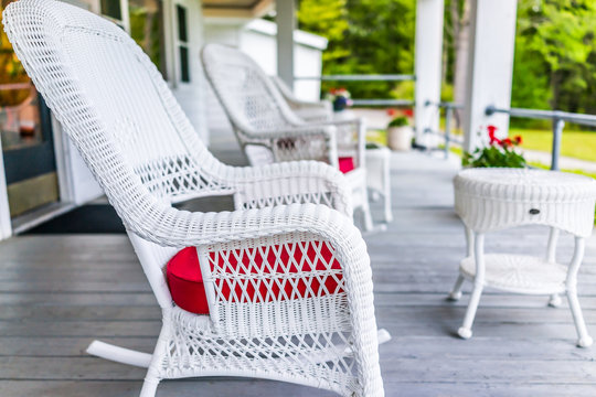 Front porch of house with white rocking chairs on wooden deck