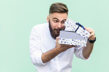 Cant stand, Its my! Curiosity young adult bearded man looking in gift box. Isolated on light green background, studio shot