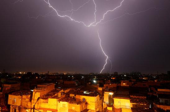 Lightning bolt is seen above a residential neighborhood during rain in Karachi,