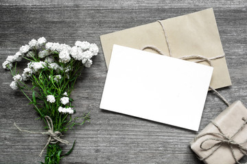 blank white greeting card with white flowers bouquet and envelope with gift box