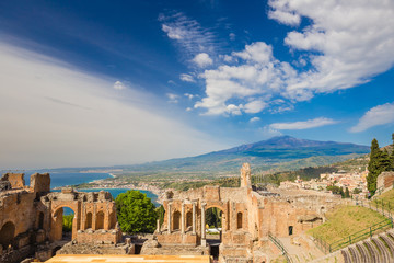 Panoramic view of beautiful town of Taormina with its greek amphitheatre and Etna volcano background, Sicily island, Italy