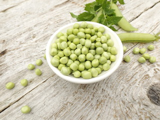 Peeled young green peas in a bowl and a bunch of mint