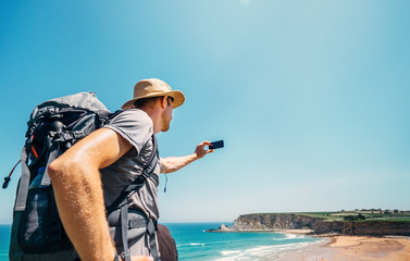 Backpacker traveler take photo beautiful ocean view with smartphone