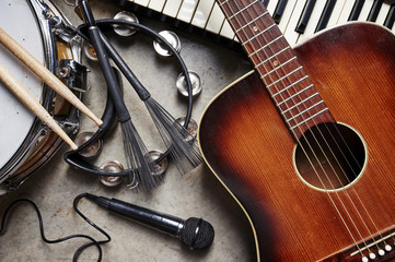 a group of musical instruments including a guitar, drum, keyboard, tambourine.