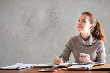 Young beautiful caucasian businesswoman thinking and working on table in a modern office