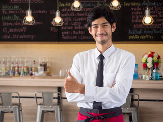 Young arab businessman/owner/barista standing front of food and beverages restaurant/cafe/shop/store with smiling face