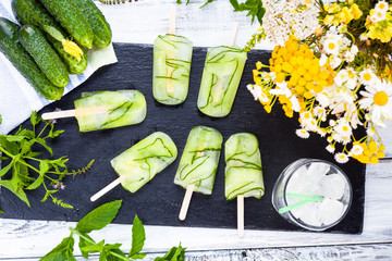 Homemade organic vegan green cucumbers popsicles. Refreshing Healthy lifestyle diet Ice pops on rustic white wooden background. Dessert ice cream for lose weight. Top view. Detox concept. Clean food.