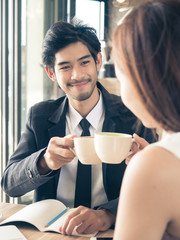 Two of young businessman / woman in casual suit talking and drinking coffee during meeting at cafe