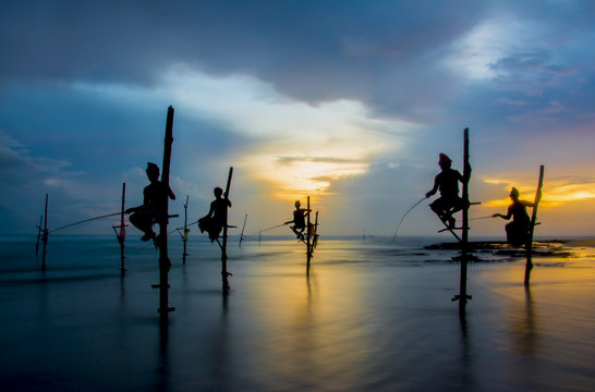 Silhouettes of the traditional Sri Lankan stilt fishermen on a stormy in Koggala, Sri Lanka. Stilt fishing is a method of fishing unique to the island country of Sri Lanka