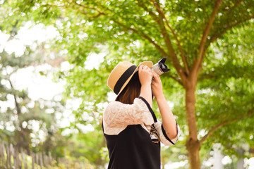 Young Asian woman is enjoy traveling into tropical forest and using mirror less camera.