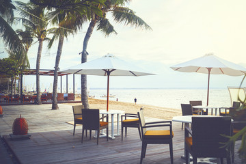 Cafe and restaurant chairs with table and umbrella at beach. Famous travel destination in Sanur, Bali, Indonesia. Wall mural