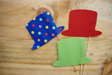 Top or flat lay view of Photo booth props a red hat, a green hat and a blue polkadot hat on a wooden background flat lay. Birthday parties and weddings.